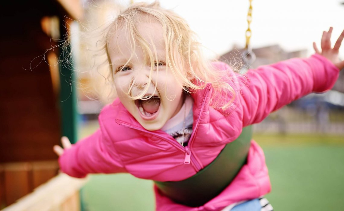 Cute little girl having fun on outdoor playground. Spring/summer/autumn active sport leisure for kids. Child on plastic swing