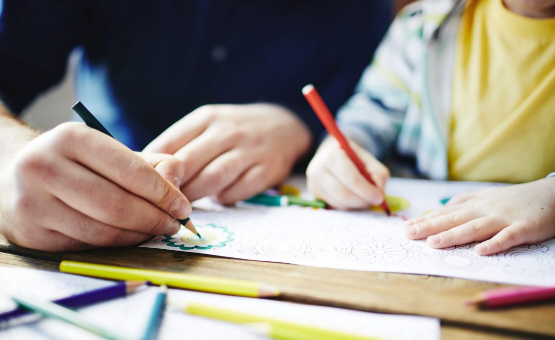 Parent and kid coloring pictures with pencils