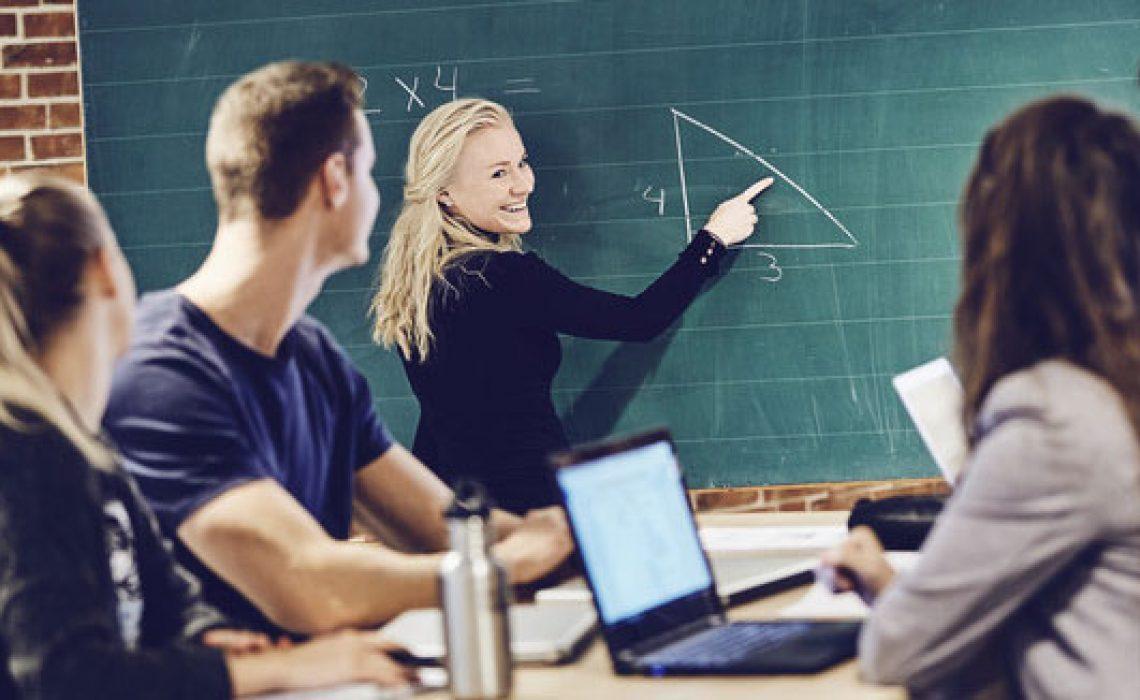 Lærerstuderende-i-færd-med-at-illustrere-regnestykke-på-tavle