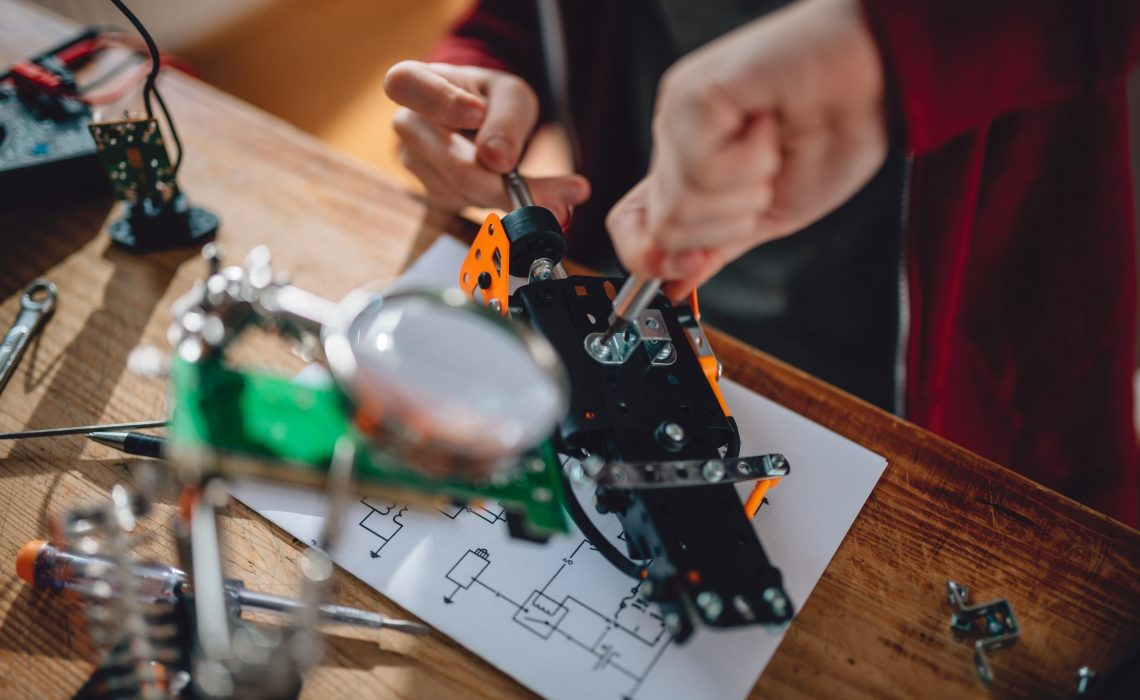 Girl building a robot on the wooden table at home as a school science project